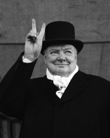 British PM Winston Churchill sporting top hat with coat and scarf as he holds up veed fingers.